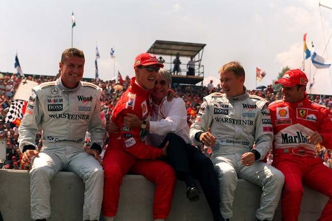 PA 372187 Snapshot: Bernie Ecclestone and Michael Schumacher are sitting on a wall