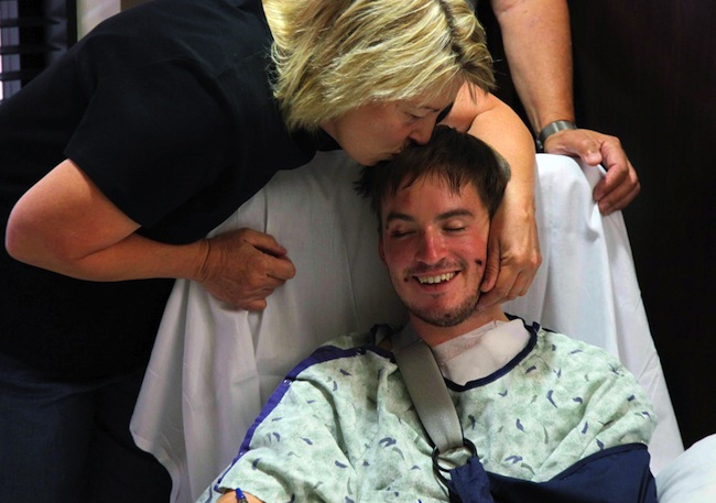 Christine Barton kisses her son Stephen Barton on July 22 at the Medical Center of Aurora in Aurora Colorado. Stephen Barton was wounded in the mass shooting. The most dramatic news photos of 2012