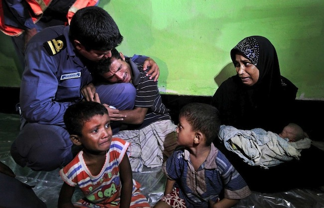 Mohammad Rafique a Rohingya Muslim from Myanmar begs a Bangladeshi coast guard official not to send his family back to Myanmar. The most dramatic news photos of 2012