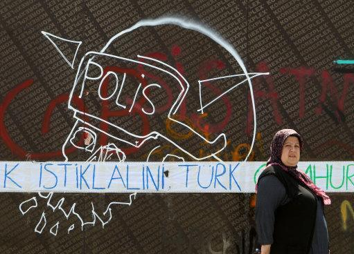 A woman passes next to a graffiti with a police helmet as the blue words reading ''Turk independence'' at Taksim Square in Istanbul, Monday, June 3, 2013. The demonstrations that grew out of anger over excessive police force have spiraled into Turkey's biggest anti-government demonstrations in years, challenging Prime Minister's Recep Tayyip Erdogan power. (AP Photo/Thanassis Stavrakis)