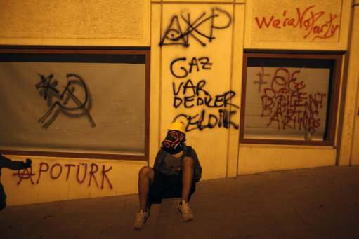 "A protester wearing a gas mask rests under a graffiti that reads ""They said they have gas""  during clashes  near Taksim square in Istanbul, early Wednesday, June 5, 2013.  Turkey's deputy prime minister offered an apology Tuesday for the government's violent crackdown on an environmental protest, a calculated bid to ease days of anti-government rallies in the country's major cities. (AP Photo/Kostas Tsironis)"
