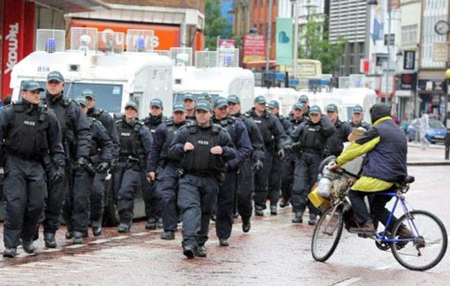 Police watch as anti G8 protesters take part in a rally in Belfast City centre ahead of the G8 world leaders summit.