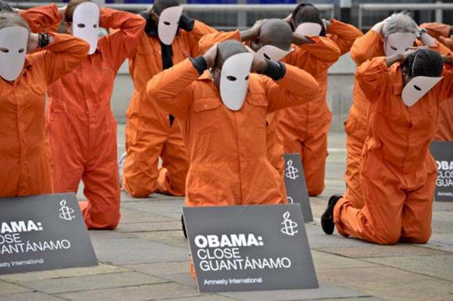 Protesters from Amnesty International dressed in orange jump suits and masks, hold placards requesting that President of the United States, Barack Obama, closes Guantanamo, as they congregate outside the Waterfront, Belfast, ahead of the G8 summit.