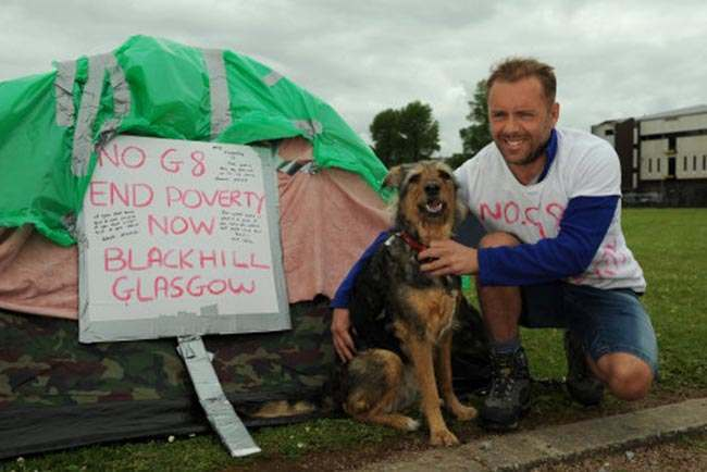 G8 protester Andrew Carnegie 43, from Glasgow, with his dog Grace at their make shift camp at Broadmeadow, Enniskillen, ahead of the G8 summit.