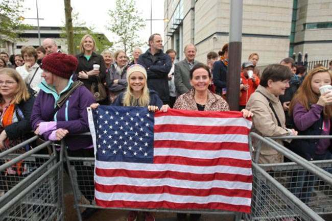Crowd members wave an American flag as Barack Obama arrives Belfast Waterfront Hall before delivering his keynote address ahead of the G8 summit.