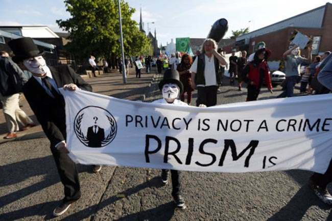 Protestors wearing masks of Guy Fawkes hold a banner during a demonstration outside of the security perimeter of the G-8 summit in Enniskillen, Northern Ireland on Monday, June 17, 2013. The summit is taking place under heavy security, with some 7,000 police lining roads and checking vehicles. (AP Photo/Lefteris Pitarakis)