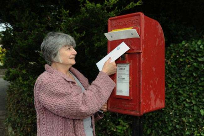 Marie Waterhouse, 68, from Enniskillen tries to post a letter at her local post box. Police have sealed off post boxes around Loch Erne Resort during the G8 Summit.