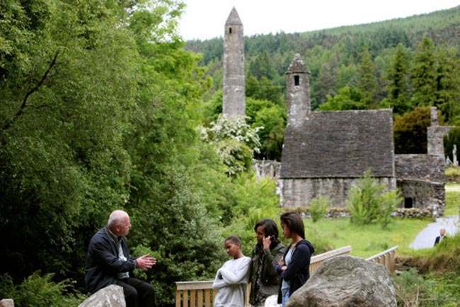 US First Lady Michelle Obama and her two daughters Malia Ann (right) and Sasha listen to Head Tour Guide George McClafferty explain about the historically important monastic site of Glendalough, Co Wicklow while he sits on the ancient Deer Stones with St. Kevin's Church and the Round Tower in the background.
