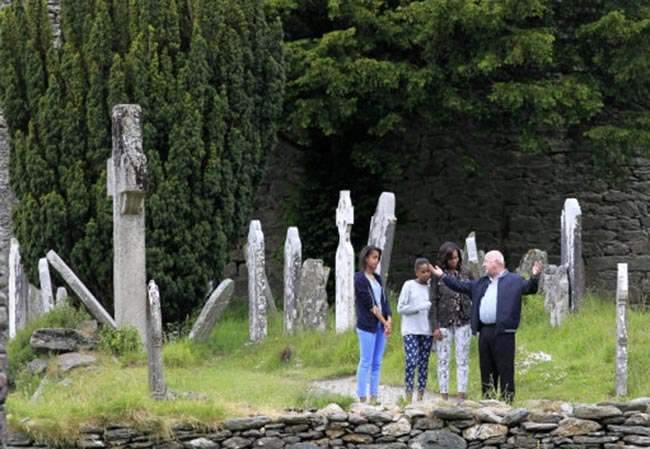 US First Lady Michelle Obama and her two daughters Malia Ann (left) and Sasha listen to Head Tour Guide George McClafferty explain about the historically important monastic site of Glendalough, Co Wicklow.