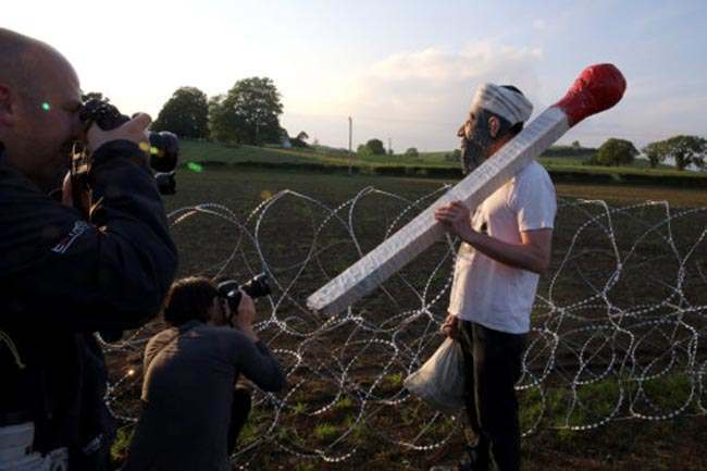 A protestor dressed as Osama Bin Laden at the security fencing yesterday as the G8 Summit continues.