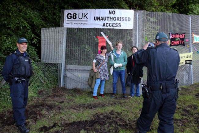 A police officer guarding security fence takes a photograph for protestors yesterday as the G8 Summit continues.