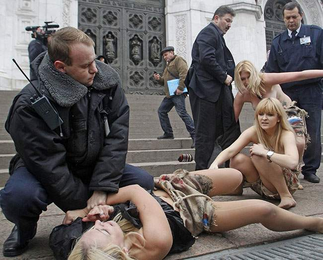 PA 12262653 FEMEN Faces: Photos of police officers expressions as they arrest topless feminists