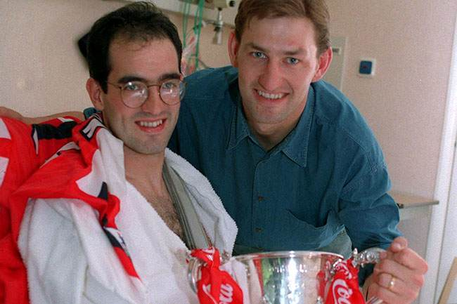 Steve Morrow (left), recovering from a broken arm, in the Clementine Churchill Hospital, is visited by his Arsenal team captain Tony Adams, with the Coca-Cola Cup that Arsenal won by beating Sheffield Wednesday.