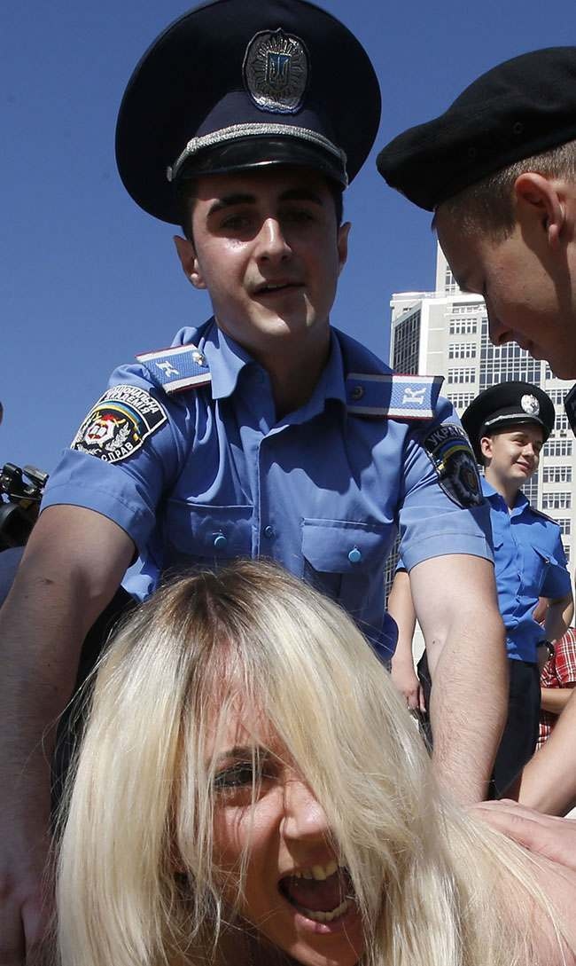 PA 13939134 FEMEN Faces: Photos of police officers expressions as they arrest topless feminists