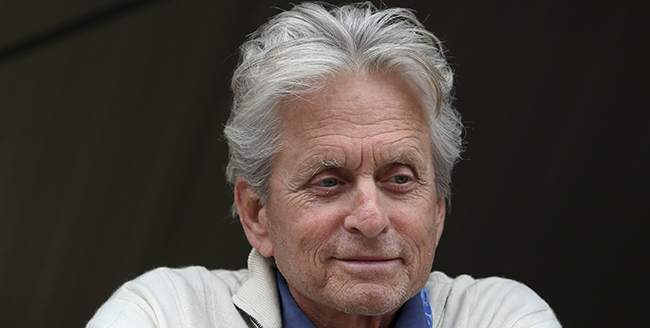 American actor Michael Douglas smiles as he watches from the Ferrari pits during the qualifying session at the Monaco racetrack in Monaco, Saturday, May 25, 2013. The Formula one race will be held on Sunday. (AP Photo/Luca Bruno)