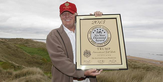 Donald Trump is pictured holding an award for The Best Golf Course Worldwide from The American Academy of Hospitality Sciences at the Trump International Golf Links, at his Aberdeenshire golf resort, in Scotland.