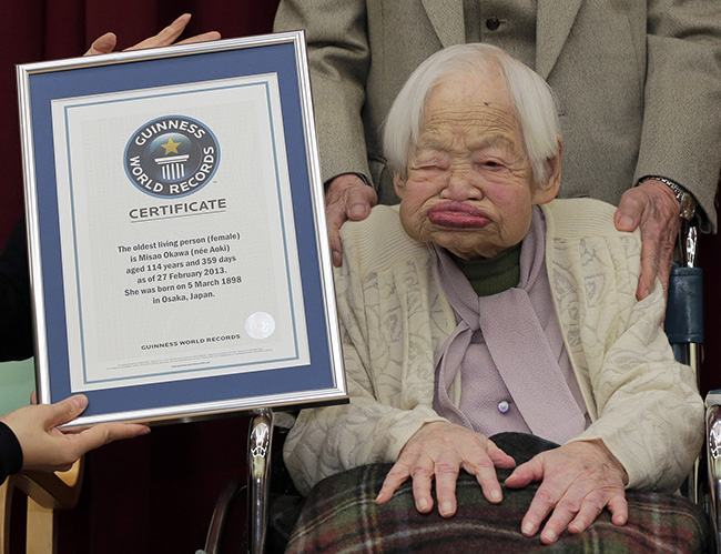FILE - In this Feb. 27, 2013 file photo, Japan's Misao Okawa, then 114, poses with the certificate of the world's oldest woman, which was presented to her by Guinness World Records Japan Country Manager Erika Ogawa, unseen, at a nursing home in Osaka, western Japan. According to Kyodo report, Guinness World Records Japan announced Wednesday, June 12, 2013 that Okawa, 115, became the world's oldest person following the death of Jiroemon Kimura who was recognized as the world's oldest living person in 2012. Kimura died of natural causes on early Wednesday at the age of 116. (AP Photo/Itsuo Inouye, File)