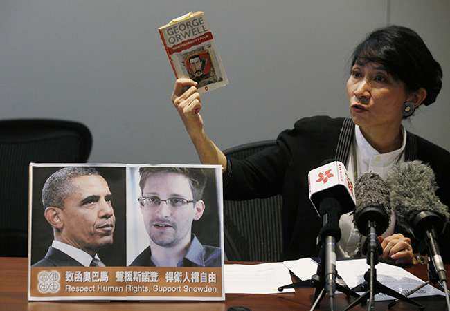 "Pro-democractic legislator Claudia Mo holds a copy of George Orwell's ""Nineteen Eighty-Four"" next to a picture of U.S. President Barack Obama and Edward Snowden during a news conference in Hong Kong Friday, June 14, 2013. Two lawmakers in Hong Kong said on Friday that they had written to U.S. President Obama to try to persuade him not to bring charges against the former US intelligence contractor Snowden. Snowden revealed last weekend he was the source of a major leak of top-secret information on NSA surveillance, saying he was uncovering wrongdoing. He spoke to reporters from an undisclosed location in the semiautonomous Chinese territory of Hong Kong. (AP Photo/Kin Cheung)"