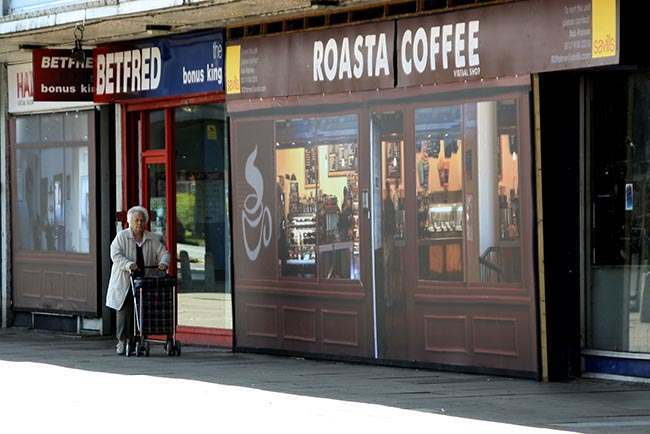 A woman walks past the 'Roasta Coffee' outlet at Coronation Square shopping centre in Hester's Way, Cheltenham as the owners of a struggling shopping centre have given it a new lease of life, by filling empty lots with fake shops.