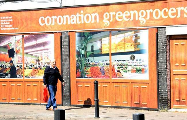 A man walks past the 'Coronation Greengrocers' outlet at Coronation Square shopping centre in Hester's Way, Cheltenham as the owners of a struggling shopping centre have given it a new lease of life, by filling empty lots with fake shops.