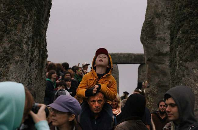 People walk during the summer solstice shortly after 04:52 am at the prehistoric Stonehenge monument, near Salisbury, England, Friday, June 21, 2013. Following an annual all-night party, thousands of New Agers and neo-pagans danced and whooped in delight at the ancient stone circle Stonehenge, marking the summer solstice, the longest day of the year. (AP Photo/Lefteris Pitarakis)