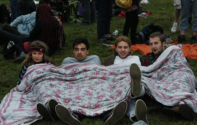 Following an annual all-night party, people rest during the summer solstice shortly after 04:52 am at the prehistoric Stonehenge monument, near Salisbury, England, Friday, June 21, 2013. Thousands of New Agers and neo-pagans danced and whooped in delight at the ancient stone circle Stonehenge, marking the summer solstice, the longest day of the year. (AP Photo/Lefteris Pitarakis)