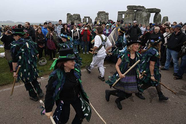 People perform in celebration during the summer solstice shortly after 04:52 am at the prehistoric Stonehenge monument, near Salisbury, England, Friday, June 21, 2013. Following an annual all-night party, thousands of New Agers and neo-pagans danced and whooped in delight at the ancient stone circle Stonehenge, marking the summer solstice, the longest day of the year. (AP Photo/Lefteris Pitarakis)