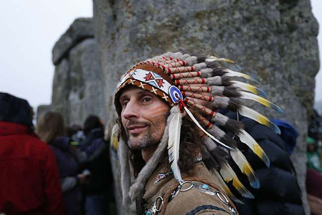 A man stands during the summer solstice shortly after 04:52 am at the prehistoric Stonehenge monument, near Salisbury, England, Friday, June 21, 2013. Following an annual all-night party, thousands of New Agers and neo-pagans danced and whooped in delight at the ancient stone circle Stonehenge, marking the summer solstice, the longest day of the year. (AP Photo/Lefteris Pitarakis)