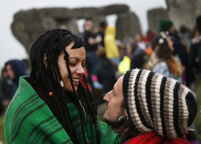 Newly engaged Karma, left, of New Zealand and Simon, right, of England, last names not given, talk during the summer solstice shortly after 04:52 am at the prehistoric Stonehenge monument, near Salisbury, England, Friday, June 21, 2013. The couple were engaged that morning on the site. Following an annual all-night party, thousands of New Agers and neo-pagans danced and whooped in delight at the ancient stone circle Stonehenge, marking the summer solstice, the longest day of the year. (AP Photo/Lefteris Pitarakis)