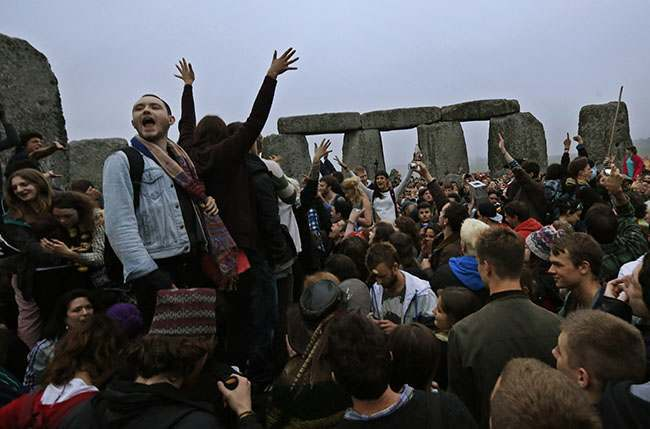 People raise their hands in celebration during the summer solstice shortly after 4:52 am at the prehistoric Stonehenge monument, near Salisbury, England, Friday, June 21, 2013. Following an annual all-night party, thousands of New Agers and neo-pagans danced and whooped in delight at the ancient stone circle Stonehenge, marking the summer solstice, the longest day of the year. (AP Photo/Lefteris Pitarakis)