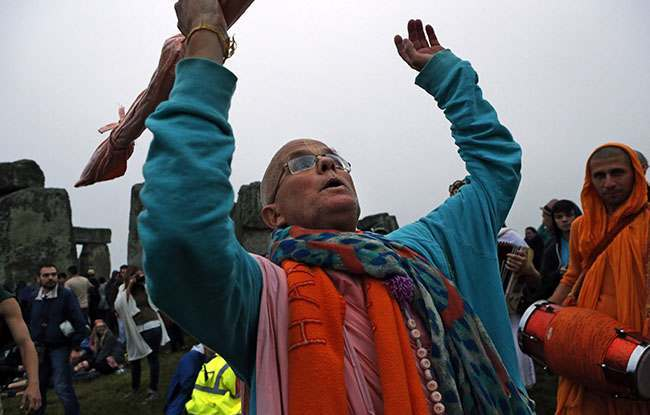 A monk dances during the summer solstice shortly after 04.52 am at the prehistoric Stonehenge monument, near Salisbury, England, Friday, June 21, 2013. Following an annual all-night party, thousands of new agers and neo-pagans waited at the ancient stone circle Stonehenge for the sun to come up, but cloudy skies prevented them. They danced and whooped in delight marking the summer solstice, the longest day of the year. (AP Photo/Lefteris Pitarakis)