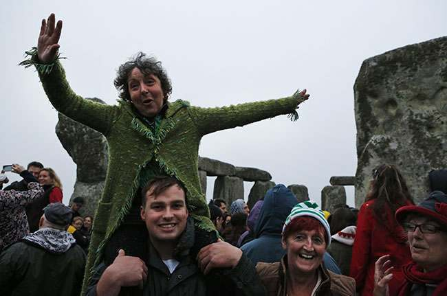 People dance during the summer solstice shortly after 04.52 am at the prehistoric Stonehenge monument, near Salisbury, England, Friday, June 21, 2013. Following an annual all-night party, thousands of new agers and neo-pagans waited at the ancient stone circle Stonehenge for the sun to come up, but cloudy skies prevented them. They danced and whooped in delight marking the summer solstice, the longest day of the year. (AP Photo/Lefteris Pitarakis)
