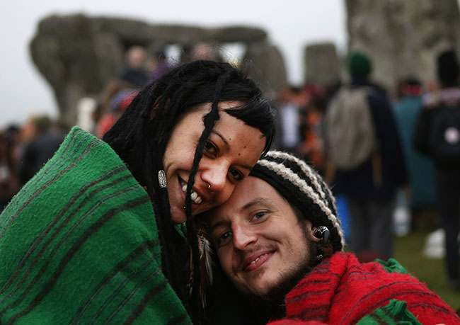 Newly engaged Karma, left, of New Zealand and Simon, right, of England, last names not given, pose for the photographer during the summer solstice shortly after 04.52 am at the prehistoric Stonehenge monument, near Salisbury, England, Friday, June 21, 2013. The couple were engaged that morning on the site. Following an annual all-night party, thousands of new agers and neo-pagans waited at the ancient stone circle Stonehenge for the sun to come up, but cloudy skies prevented them. They danced and whooped in delight marking the summer solstice, the longest day of the year. (AP Photo/Lefteris Pitarakis)