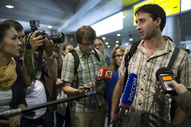 "An unidentified passenger, right, who just arrived from Hong Kong and said to waiting journalists that he had seen former CIA employee who leaked top-secret documents about sweeping U.S. surveillance programs Edward Snowden, aboard his flight from Hong Kong, as the unidentified passenger speaks to journalists at Sheremetyevo airport, just outside Moscow. Russia, Sunday, June 23, 2013. The former National Security Agency contractor Snowdon, wanted by the United States for revealing two highly classified surveillance programs has been allowed to leave Hong Kong for a ""third country"" because a U.S. extradition request did not fully comply with Hong Kong law, the territory's government said Sunday.(AP Photo / Alexander Zemlianichenko)"