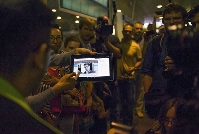 "Journalists show passengers arriving from Hong Kong a tablet with a photo of Edward Snowden, a former CIA employee who leaked top-secret documents about sweeping U.S. surveillance programs, at Sheremetyevo airport, just outside Moscow, Russia, Sunday, June 23, 2013. The former National Security Agency contractor wanted by the United States for revealing two highly classified surveillance programs has been allowed to leave for a ""third country"" because a U.S. extradition request did not fully comply with Hong Kong law, the territory's government said Sunday. (AP Photo/Alexander Zemlianichenko)"