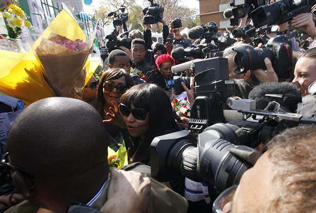 Granddaughters Zaziwe Dlamini-Manaway, center, and Tukwini Mandela, center left, are swamped by the media after collecting flowers from wellwishers outside the Mediclinic Heart Hospital where former South African President Nelson Mandela is being treated in Pretoria, South Africa Thursday, June 27, 2013. President Jacob Zuma canceled a trip to Mozambique on Thursday in an indication of heightened concern about Mandela, whose health deteriorated last weekend. (AP Photo/Themba Hadebe)
