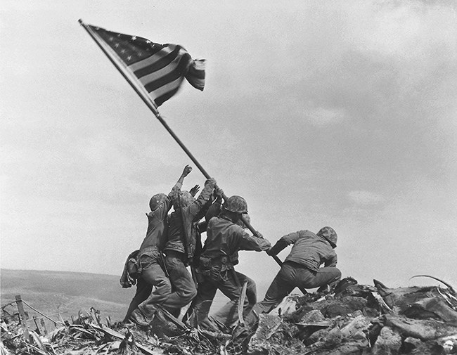 **FILE** U.S. Marines of the 28th Regiment of the Fifth Division raise the American flag atop Mt. Suribachi, Iwo Jima, in this file photo of Feb. 23, 1945. A search team is on the island of Iwo Jima looking for a cave where the Marine combat photographer who filmed the famous World War II flag-raising 62 years ago is believed to have been killed in battle nine days later, military officials said Friday, June 22, 2007. Sgt. Willam H. Genaust, a combat photographer, used a movie camera to film the raising of the flag atop Mount Suribachi, standing just feet away from AP photographer Joe Rosenthal, who took this iconic photograph. (AP Photo/Joe Rosenthal, File)