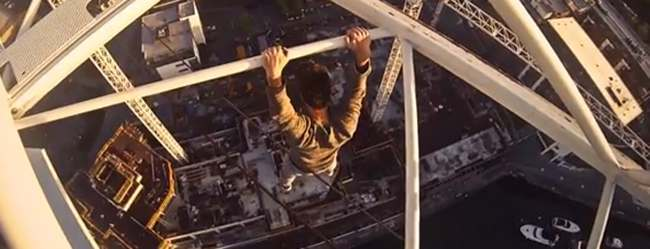 james kingston Thrill seeker climbs very tall crane in Southampton then dangles off it with one hand (video)