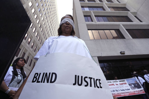 "Ethel Bradford stands dressed as 'blind justice' at a ""Justice for Trayvon"" rally in New Orleans, Saturday, July 20, 2013. The Rev. Al Sharpton's National Action Network organized ""Justice for Trayvon"" rallies nationwide to press for federal civil rights charges against George Zimmerman, who was found not guilty in the shooting death of unarmed teenager Trayvon Martin. (AP Photo/Gerald Herbert)"