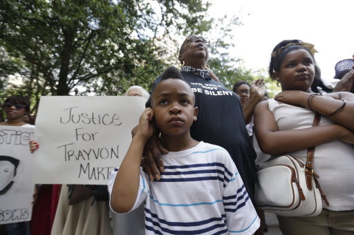 "Tommie Butler, 6, stands with his grandmother Sharon Jasper at a rally held in reaction to the recent George Zimmerman acquittal in New Orleans, Saturday, July 20, 2013. The Rev. Al Sharpton's National Action Network organized ""Justice for Trayvon"" rallies nationwide to press for federal civil rights charges against George Zimmerman, who was found not guilty in the shooting death of unarmed teenager Trayvon Martin. (AP Photo/Gerald Herbert)"
