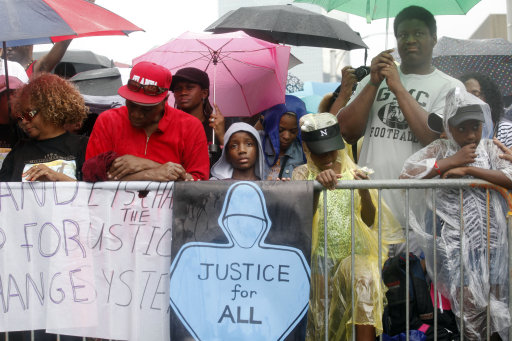 "Elijah Ash, 8, holds up a ""justice for all"" sign as it rains during a rally outside the Richard B. Russell Federal Building, Saturday, July 20, 2013, in Atlanta. The Rev. Al Sharpton's National Action Network organized ""Justice for Trayvon"" rallies nationwide to press for federal civil rights charges against George Zimmerman, who was found not guilty in the shooting death of unarmed teenager Trayvon Martin. (AP Photo/Jaime Henry-White)"