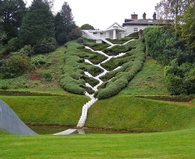 The Universe Cascade is located on a slope that runs down the back of the Gardens of Cosmic Speculation (Dumfries, Scotland), forming an axis between the snail mound and the rear of the house and consists of a steep series of steps. link A giant rock and a bench for contemplation were installed at each level for individuals to use as they climbed steeply upwards. link The staircase is an extraordinarily dramatic structure rising up from a large pond, water pouring down the centre as it criss-crosses the steep hillside, and ends in an open pavilion at the top. Though the gardens are private, they open to the public once a year.