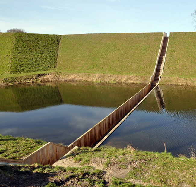"arly 17th century Fort de Roovere is surrounded by a moat and was originally built without a bridge. Yet, as part of a recent restoration program, it required the addition of an access bridge. link Out of respect for the fort's original island status, Netherlands-based RO&AD Architecten  constructed the Moses Bridge Stairs, a discreet ""sunken"" bridge that sits flush with the line of the soil and the water. The result is an almost invisible bridge that partially immerses pedestrians into the moat. link Originally, an inundation zone to the north provided an area that could be flooded with water deep enough to make enemy advance on foot precarious, yet shallow enough to rule out the effective use of boats. link Today, two dams sit at either end of the mote, ensuring that when the water level rises, it spills over the dams and not into the bridge. [link, map]"