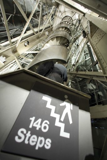In this May 20, 2009 photo, a sign indicates the number of stairs to the top as a journalist ascends the narrow spiral staircase to the crown inside the Statue of Liberty in New York. Had the smoke alarm of July 21, 2010 not been a malfunction and there had actually been a fire in the 125-year-old structure, the New York City fire department and National Parks service were prepared to fight it with fireboats and equipment already in place on the island. (AP Photo/Richard Drew, File)