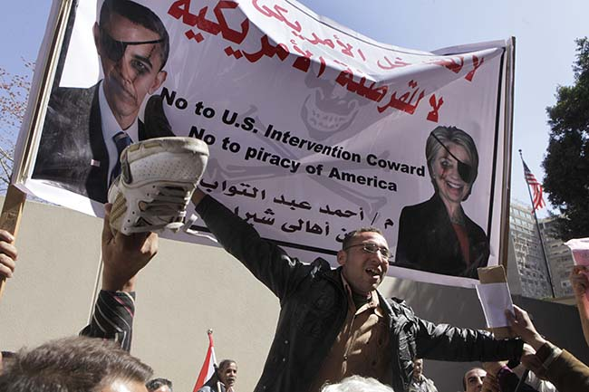 Egyptians shout anti-US slogans and raise their shoes in front of the American embassy in Cairo, Egypt, Friday March 9, 2012 as they protest against what they say is American intervention in Egypt. At top left, a poster shows U.S. President Barack Obama and at right U.S. Secretary of State Hillary Rodham Clinton. Several hundred protesters gathered Friday outside the U.S. Embassy in Cairo, raising their shoes at a picture of President Barack Obama and calling on Egypt to expel Washington's ambassador amid a heated national debate about the trial of Americans working with pro-democracy groups who have been charged with using foreign funding to foment unrest.(AP Photo/Amr Nabil)