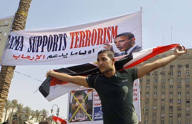 "An Egyptian anti-President Mohammed Morsi protester waves a national flag in front of a banner criticizing U.S. President Barack Obama and Mohammed Morsi in Tahrir Square, the focal point of Egyptian uprising, in Cairo Sunday, June 30, 2013. Thousands of opponents and supporters of the president began massing in city squares in competing rallies Sunday, gearing up for a day of massive nationwide protests that many fear could turn deadly as the opposition seeks to push out Mohammed Morsi. Arabic reads, ""Leave."" (AP Photo/Amr Nabil)"