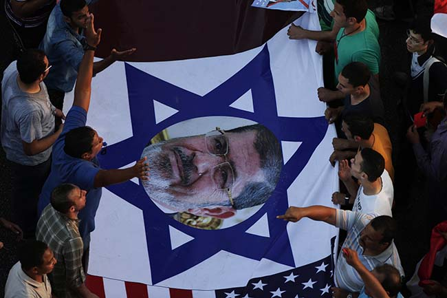 Protesters hold a banner with Islamist President Mohammed Morsi's photograph and Israel's flag during a protest outside the presidential palace in Cairo, Egypt, Sunday, June 30, 2013. Hundreds of thousands of opponents of Egypt's Islamist president poured out onto the streets in Cairo and across much of the nation Sunday, launching an all-out push to force Mohammed Morsi from office on the one-year anniversary of his inauguration. Fears of violence were high, with Morsi's Islamist supporters vowing to defend him. (AP Photo/Hassan Ammar)