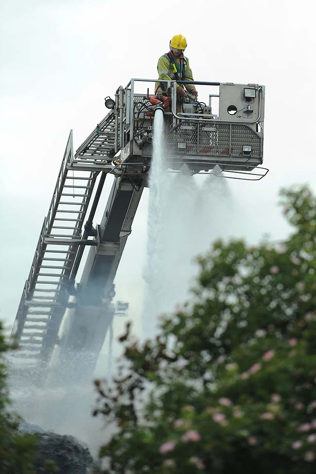 A firefighter uses a hydraulic platform during a fire at J&A Young in Smethwick, Birmingham, as more than 200 firefighters tackle a blaze at the plastics recycling plant.