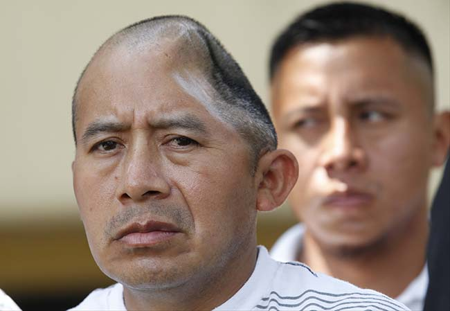 Antonio Lopez Chaj, left, a 43-year-old house painter, appears with his brother, Pedro Chang, right, at a news conference in Los Angeles Monday, July 1, 2013. Lopez Chaj is so badly brain damaged for a beating in a bar that left him with half his skull permanently bashed in that he cannot speak. His lawyers announced he has been awarded a $58 million by a jury in Torrance Superior Court. (AP Photo/Nick Ut)