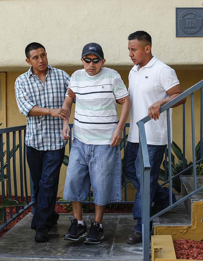 Antonio Lopez Chaj, a 43-year-old house painter, middle, is assisted to walk down the stairs by his nephew, Eric Chaj, left, and his brother, Pedro Chaj, right, to appear at a news conference in Los Angeles Monday, July 1, 2013. Lopez Chaj is so badly brain damaged for a beating in a bar that left him with half his skull permanently bashed in that he cannot speak. His lawyers announced he has been awarded a $58 million by a jury in Torrance Superior Court. (AP Photo/Nick Ut)